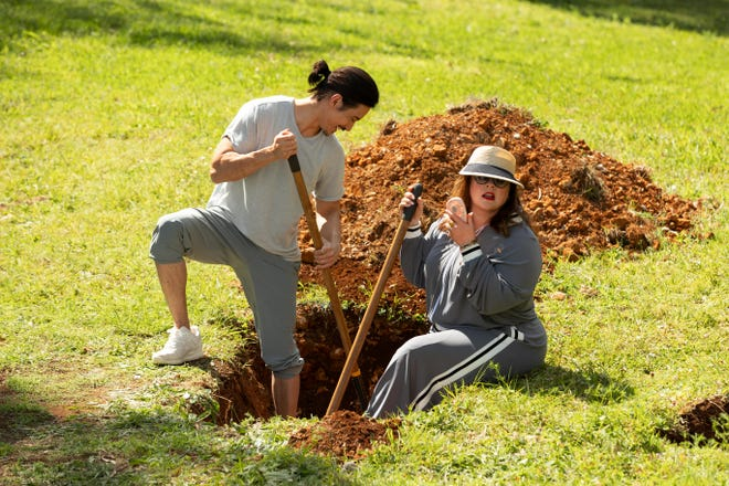 Yao (Manny Jacinto, left) and Frances (Melissa McCarthy) dig a grave in one of Masha's eeriest exercises.