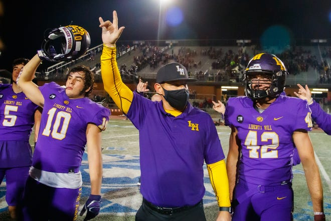 Liberty Hill head coach Kent Walker celebrates with linebacker Andon Thomas, left, and the graduated Blake Simpson after winning the Class 5A Division II Region IV championship game against the Pioneer Diamondbacks last season.