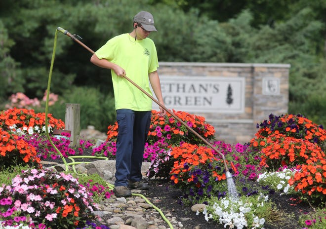 Mason Bice, a worker from the village of Reminderville, waters flowers on the roundabout. The village saw the largest percentage of population growth in Summit County, according to the 2020 census.