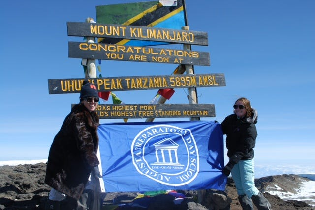Ruthie Magruder (right) and her mother, Lillian Magruder, hold up an Augusta Preparatory Day School flag at the top of Mount Kilimanjaro, the highest mountain in Africa. The flag was among family mementos they carried to the summit.