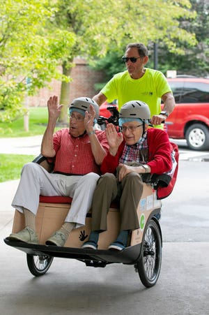 Bernie Speyer, 89, left, and Conrad Minnich, 90, right, wave as they return from a ride piloted by volunteer, Gary Blumberg, at Creekside at the Village independent living facility. The rides are offered by the newly created Columbus chapter of Cycling Without Age, a global program that offers seniors safe rides on a trishaw.