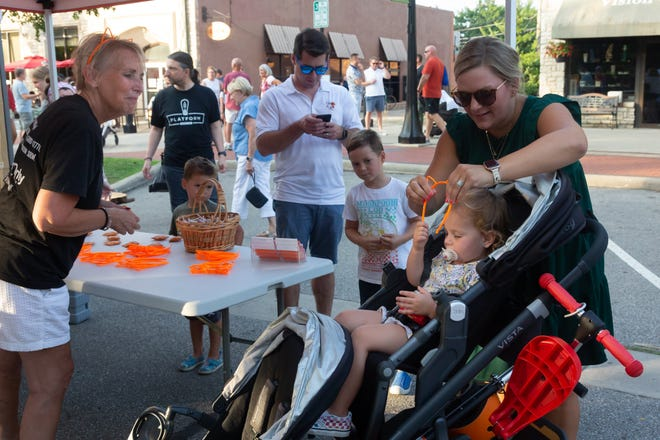 Jill Burgason of Cats Only Veterinary Clinic gives Marie Svoboda, 2, of Upper Arlington a set of cat ears Aug. 18 during the first Upper Arlington Night Market at the Mallway.