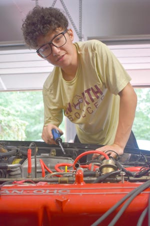 Alex Guy, 18, works on the engine of his 1981 Datsun 280ZX.