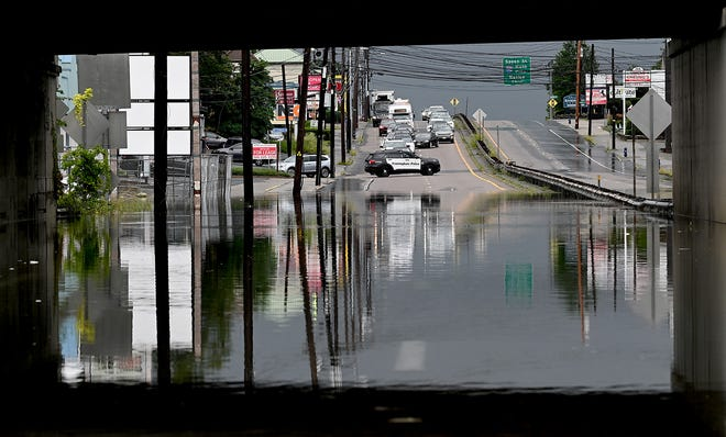 A Framingham police cruiser blocks all traffic on Rte. 9 westbound after rain from the remnants of Tropical Storm Fred flooded Rte. 9 at the Rte. 126 underpass in Framingham, Aug. 19, 2021. East and westbound lanes in the flood-prone area were closed for much of the afternoon Thursday.