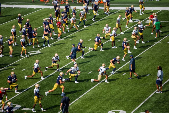 Players warm up during football practice Thursday, Aug. 19, 2021 at Notre Dame Stadium in South Bend.