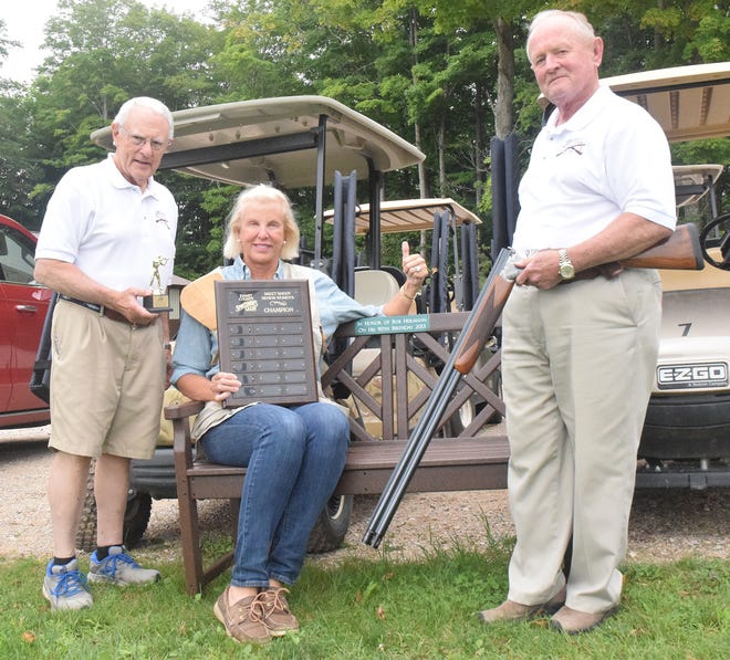 Emmet County Sportsmen's Club past president Bill Sutton (left) and current president George Moilanen (right) present Lotsie Holton with a commemorative plaque after Holton won a recent skeet shooting tournament at the club. Holton is also sitting on a bench dedicated to her father, Bob Hermann, who was a longtime member of the club.