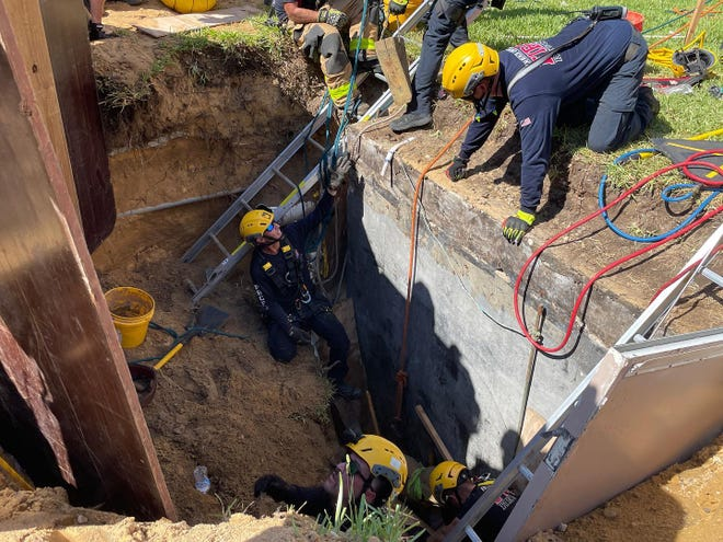 Palm Beach County Fire Rescue crews work the scene of a construction accident in Juno Beach on Thursday, Aug. 19, 2021. Three people were rescued from a 10-foot deep hole