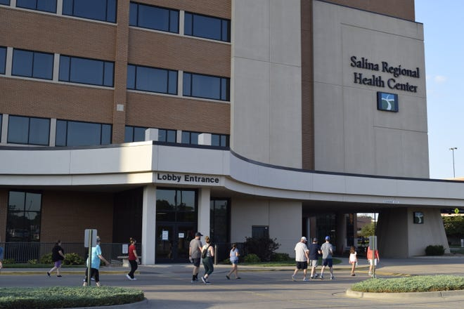 A group of community members makes their way back to the entrance of Salina Regional Health Center after a prayer walk Wednesday evening. The roughly 50 people prayed for and supported patients and healthcare workers as they walked around the hospital grounds.