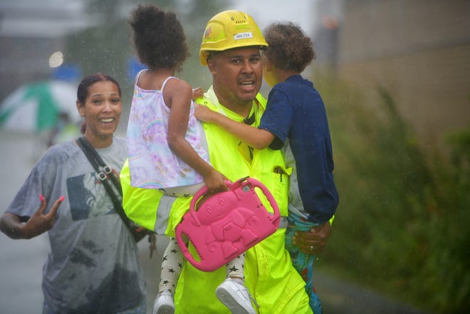 Ricardo Reyes, a construction worker for R.H. White of Auburn, rescues Vanny Lima's children.
