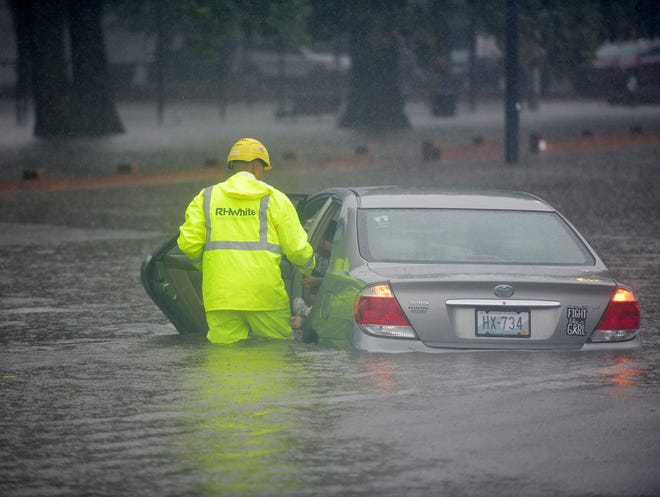 Motorist Vanny Lima and two young children were stuck in rising floodwaters on Quinsigamond Avenue near Crompton Park Thursday morning. They were aided by Ricardo Reyes, a construction worker for R.H. White of Auburn. The family was given shelter at the nearby Worcester Regional Transportation Authority building.