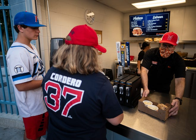 Kyle Gavin serves up southern style BBQ at BT's Smokehouse during the WooSox game on Wednesday. The popular concession stand is in the right field corner.