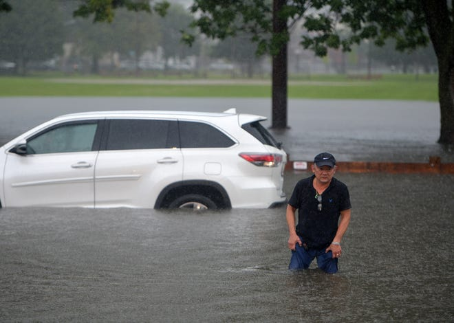 A man steps from his car in floodwaters on Quinsigamond Avenue in Worcester. The waters were spreading into Crompton Park, in the background.