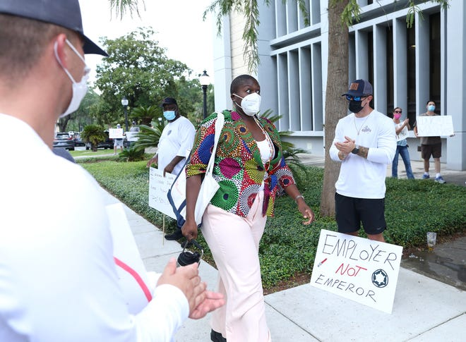 Gainesville City Commissioner Gail Johnson, center, who voted against the city's vaccine mandate, looks surprised by a round of applause given to her Aug. 19 by Gainesville Fire Rescue and Gainesville Regional Utilities employees as they protest the requirement.