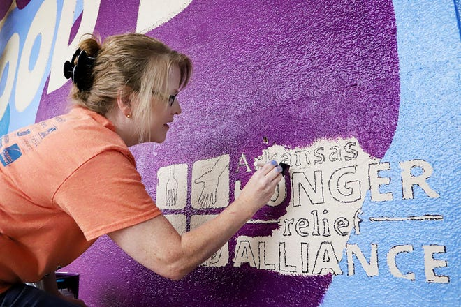 Kathy Watson with Congressman John Boozman's Fort Smith office, joins other volunteers painting a new Cole Stufflebeam store front design at the River Valley Regional Food Bank, 1617 S. Zero St. as a part of the United Way of Fort Smith Area's Day of Caring in 2019.