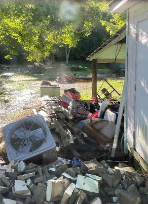 Debris from upstream on the flooded Pigeon River, including a fan, still remained on the McCracken property on Aug. 19, two days after historic flooding in the Cruso area in Haywood County.