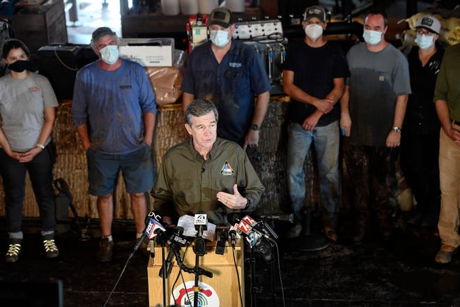 North Carolina Governor Roy Cooper stands in front of a row of muddied volunteers as he speaks to the press at BearWaters Brewing in Canton August 19, 2021.