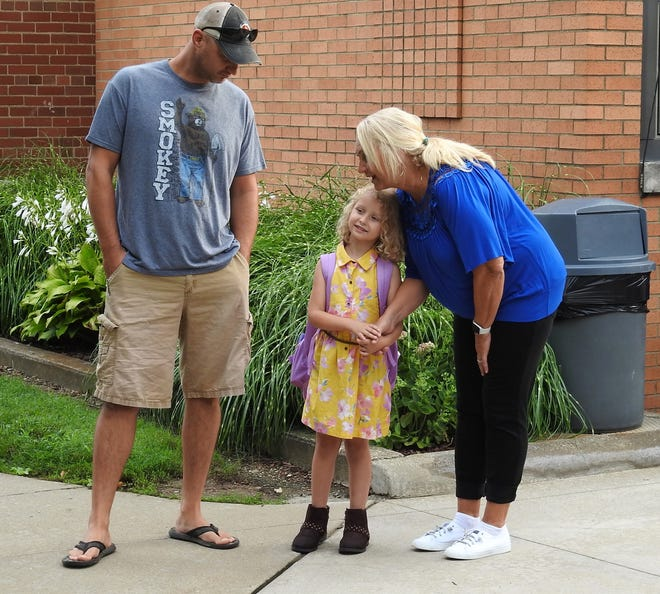 Robbie Miller and Lynn Karr wait with kindergartner Adalyn Miller to start her first day of school at Warsaw Elementary School on Thursday. The school has about 450 students.