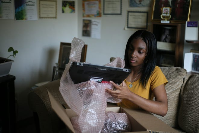 Amariah Wims-Fuller, 14, of Detroit, unboxes a laptop provided by Human-I-T at her home in Detroit on June 21, 2021. Wims-Fuller is a recent graduate of the Detroit Academy of Arts and Sciences. The city of Detroit and Human-I-T are partnering together to distribute at least 1,000 refurbished computers to students and families in Detroit.
