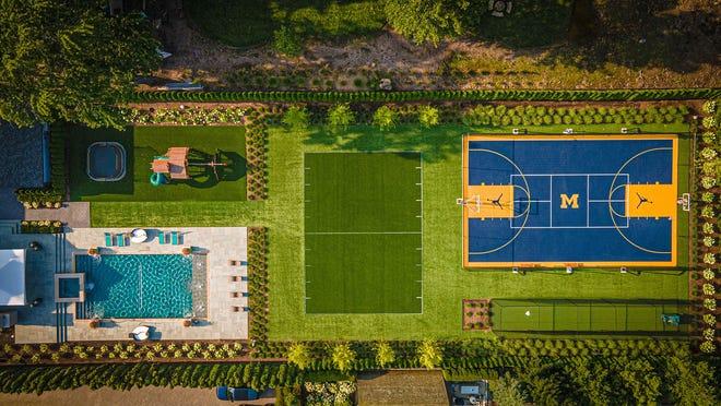 Quasi tutti gli sport a cui puoi pensare sono costruiti nel parco di questa città.  In senso orario da sinistra in alto, c'è un trampolino, un parco giochi, un campo da calcio parziale, un campo sportivo per tennis, basket e hockey, una gabbia di battuta e una piscina con rete da pallavolo.