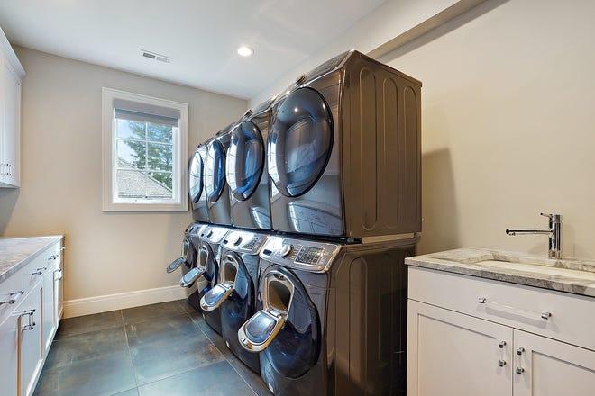 Locale lavanderia attrezzato per una famiglia numerosa con molti ospiti con quattro lavatrici e quattro asciugatrici.
