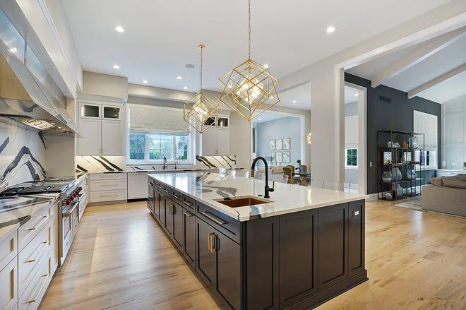 Un forte motivo bianco e nero in quarzo compone tutti i banconi e gli alzatine di questa cucina.