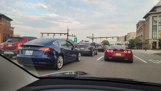 Teslas from the Tesla Owners Club of Michigan surround a Corvette in Birmingham.