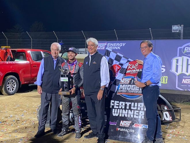 Kyle Larson (second from left) won the BC39 Stoops Pursuit race at the IMS dirt track Wednesday night. He's shown with Roger Penske (left), Mark Miles (second from right) and Doug Boles.