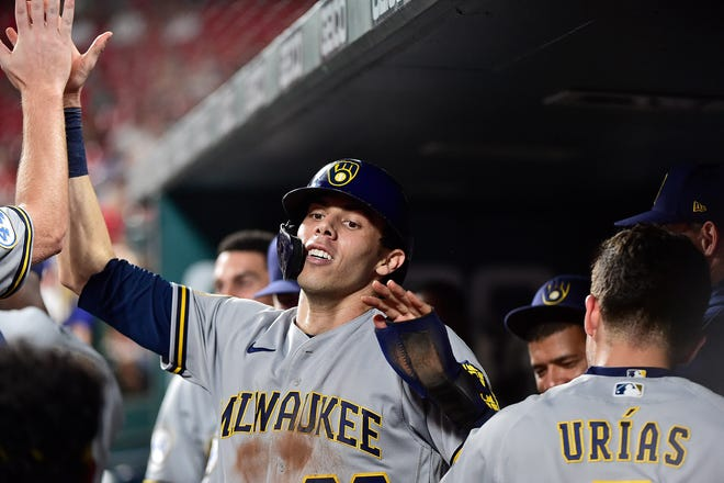Christian Yelich celebrates with teammates after scoring from first during the Brewers' 10th-inning outburst against the Cardinals on Wednesday night.