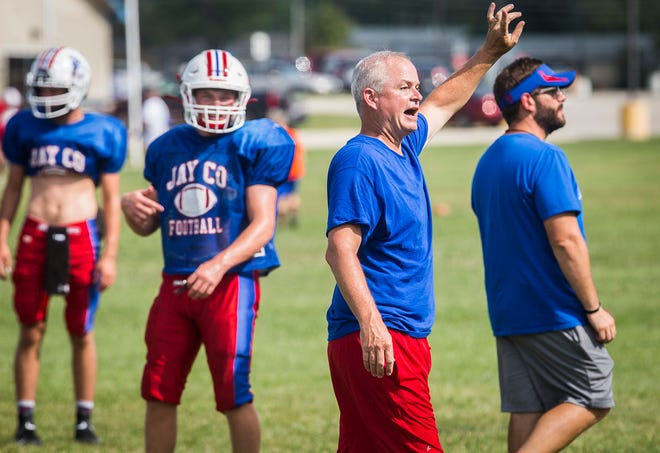Jay County football coach Grant Zgunda instructs the team during a practice outside of Jay County High School Wednesday, Aug. 19, 2021.