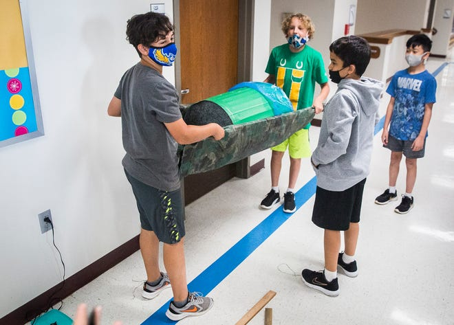 """Burris fifth through seventh grade students work on  an IMPACT project in the hallways of Burris Laboratory School Thursday, Aug. 19, 2021. Students were required to use math, reading comprehension and creativity to construct water carrying devices after reading the novel """"A Long Walk to Water""""."""