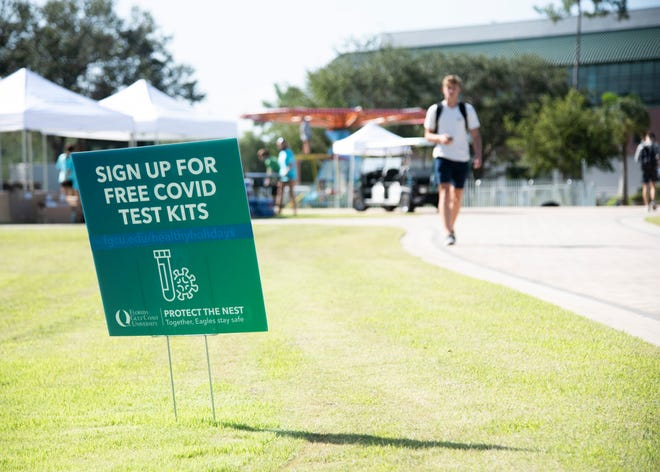 """A sign reads """"Sign up for free COVID test kits"""" on the first day of school at Florida Gulf Coast University on Thursday, August 19, 2021."""