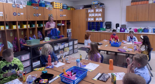 First grade teacher Allyson Ray helps students organizes their classroom materials and find their cubbies during the first day of school on Thursday, Aug. 19, 2021 at Newark City School's Hillview Elementary.