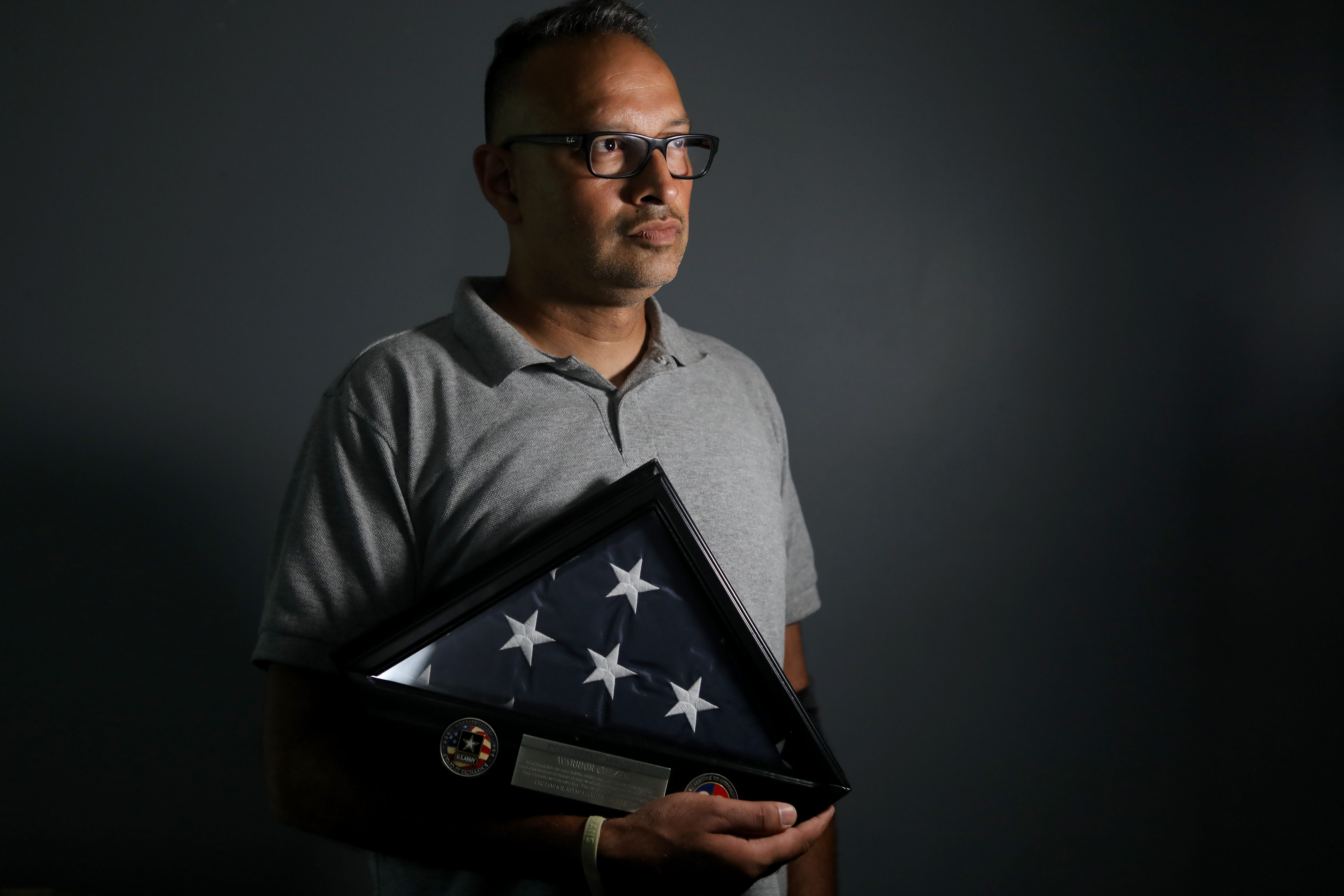 Farhaj Hassan, a Muslim American soldier from Helmetta, New Jersey, was in basic training on Sept. 11, 2001. Here he poses with a flag he was awarded after serving among the first rotation of military members deployed in Operation Iraqi Freedom.