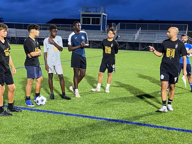 Wood-Ridge boys soccer Coach Alberico De Pierro, far right in black, goes over assignments for the drill Wednesday night.