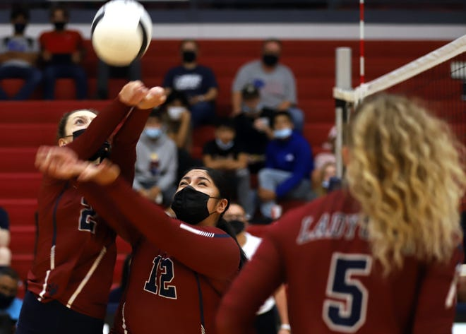 At left, Lilly McMillan and Victoria Baca keep the ball up during a Lady 'Cat rally.