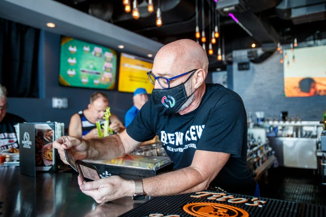 Hunters Nightclubs Palm Springs operations manager Troy Hay checks a patron's proof of vaccination against COVID-19 at the bar in Palm Springs, Calif., on August 18, 2021.