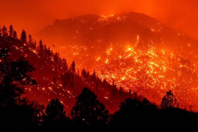 Seen in a long exposure photograph, embers light up hillsides as the Dixie Fire burns near Milford in Lassen County, Calif., on Tuesday, Aug. 17, 2021. (AP Photo/Noah Berger)
