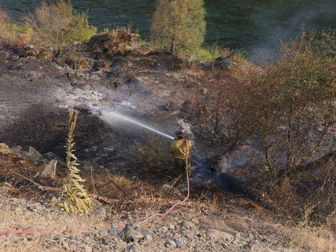 Forest Service Engine Capt. Diego Alvarez puts out a hot spot from the monument Fire along the Trinity River on Tuesday, Aug. 17, 2021.