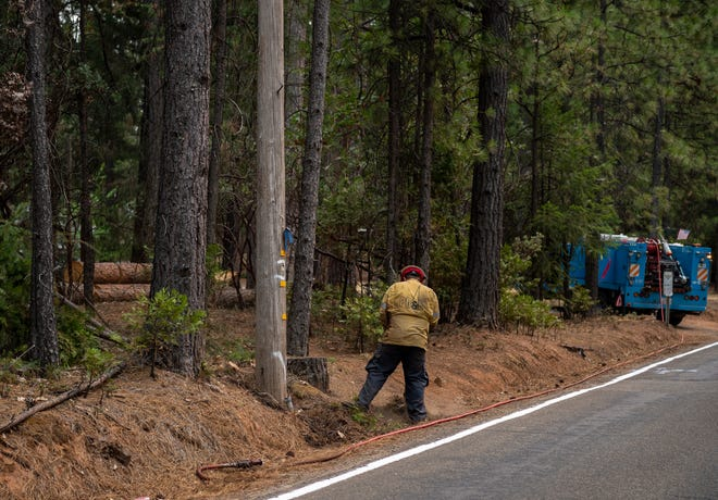 A PG&E employee clears brush on the side of the road amid the Caldor Fire on Wednesday, August 18, 2021.
