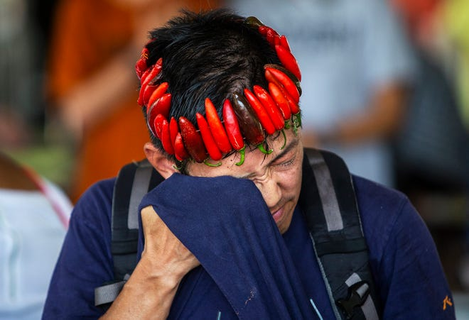 Blake Tatsuta, sporting a homemade crown of serrano and jalapeño peppers picked from his pepper plants, carefully wipes sweat from his brow while tasting hot sauces during the 28th annual Austin Chronicle Hot Sauce Festival at Fiesta Gardens in 2018.