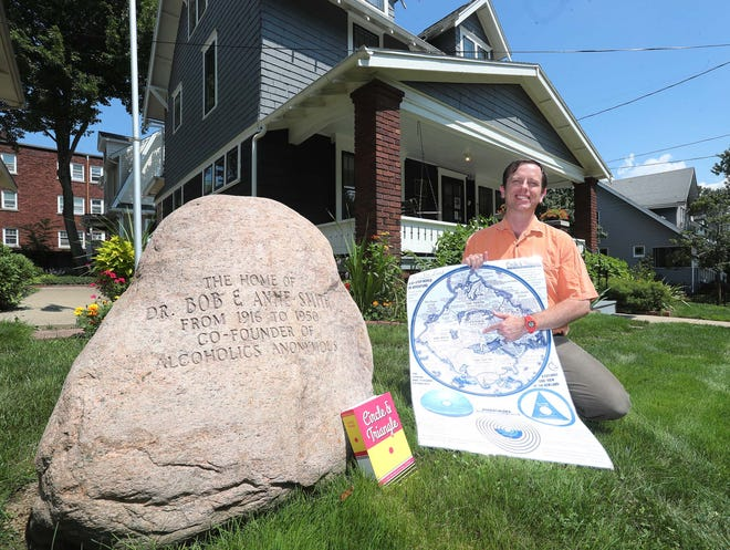 New York resident Travis Henry, who has created a fantasy role-playing game based on 12-step principles, sits Aug. 20 outside the home of Alcoholics Anonymous co-founder Dr. Bob Smith on Ardmore Avenue in Akron. The game Circle & Triangle is set in a fantasy world based on Akron with Dr. Bob's House at the center.