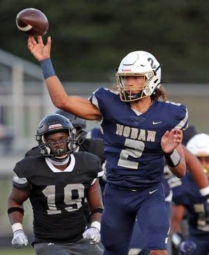 Akron Hoban quarterback Jayvian Crable throws a pass against Bishop Sycamore on Aug. 19. Hoban won 38-0.