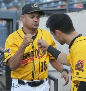 RubberDucks hitting coach Junior Betances fist bumps Steven Kwan before the start of a game against the Harrisburg Senators on Wednesday. Betances has helped the Ducks become one of the Double-A Northeast's most potent offenses. [Phil Masturzo/ Beacon Journal]