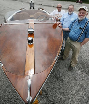 Ken Shumaker, 81, front, and his brothers Dick, 80, and Jim, 78, stand next to their restored 1956 motorboat before launching it Wednesday at Turkeyfoot North Shore Park in New Franklin. The Akron brothers saved money from their Beacon Journal newspaper routes in the 1950s to buy the Cruisers Holiday.