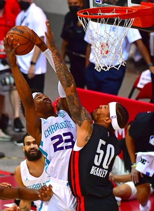 Charlotte forward Kai Jones goes up for a dunk against Portland's Michael Beasley during an NBA Summer League game Aug. 8. Jones wears No. 23, made famous by Hornets owner Michael Jordan.