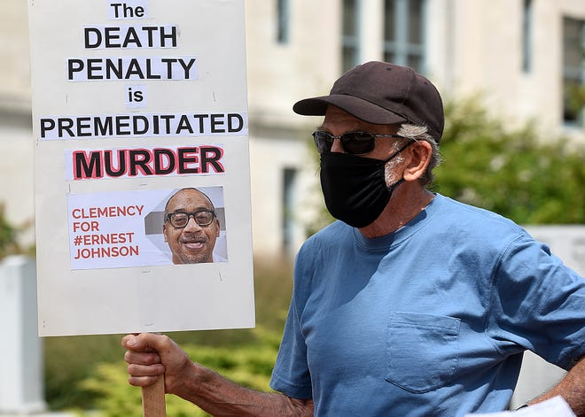 Vic Myers of Columbia holds a sign during a protest at the Boone County Courthouse opposing the death penalty for Ernest Lee Johnson, who was convicted of three 1994 killings at a Casey's General Store in Columbia. Activist groups, members of Congress, a former Missouri governor and the pope are asking Gov. Mike Parson to grant Johnson clemency.
