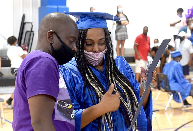 Drew Down and his wife, Marquitta Spain, look at the certified nursing assistant certificate she received Friday during Job Point's graduation ceremony at the Boys & Girls Clubs of Columbia.