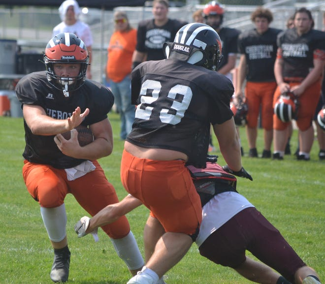 Cheboygan's Beau Ginop, left, breaks a tackle while his brother, Gauge Ginop (23), makes a block on a Charlevoix player during a varsity football scrimmage at Western Avenue Field on Friday.