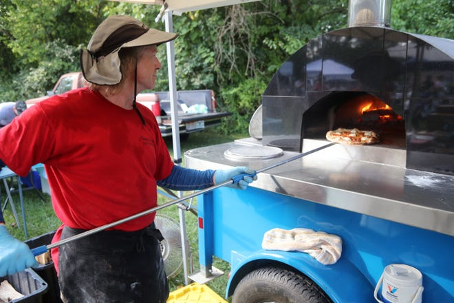 Pompeii's Inferno owner John Glavocich pulls a pizza from a wood-fired oven Aug. 19 during the Olde Pickerington Farmers Market. The market is held 4-7 p.m. each Thursday through Sept. 30 at 89 N. Center St.