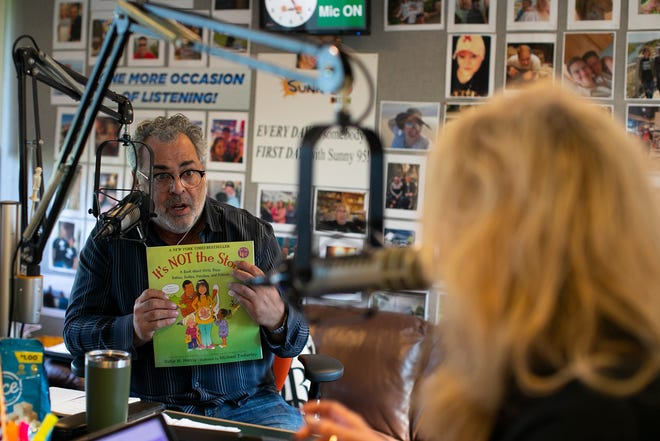 """Morning show radio personality at WSNY (94.7 FM) Dino Tripodis displays a children's book called """"It's NOT the stork!"""" to longtime co-host Stacy McKay during an Aug. 20 broadcast of """"Sunny This Morning with Stacy McKay & Dino Tripodis."""" Tripodis was at Sunny 95 for 24 years before he left in 2018 to pursue his own creative projects. He returned in July."""